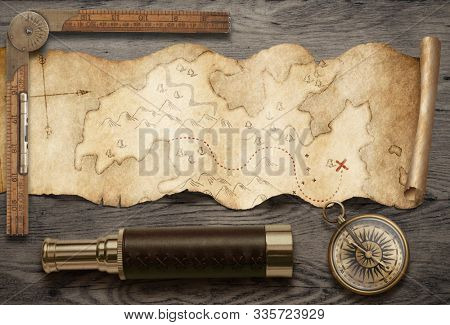 Old torn treasure map with compass and spyglass top view still life. Adventure and travel concept. Mixed media.