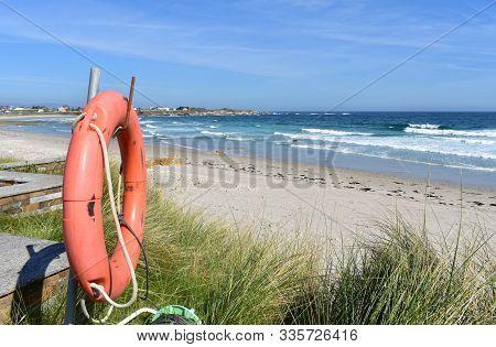 Beach With Life Saver, Grass And Waves. Viveiro, Lugo Province, Spain.