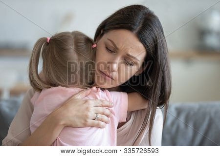 Worried Young Foster Mother Comforting Embracing Adopted Child Daughter