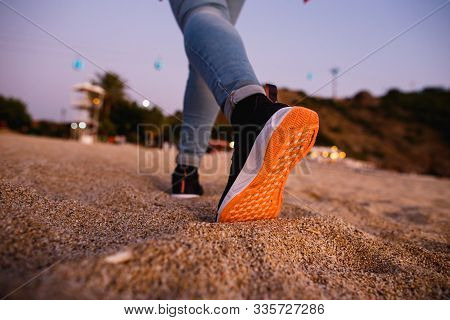 Girl Feet In Sneakers With Bright Orange Soles Go Away On The Sand. Concept For Start, Going, Step F
