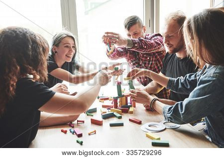 A Group Of Creative Friends Sitting On A Wooden Table. People Were Having Fun While Playing A Board