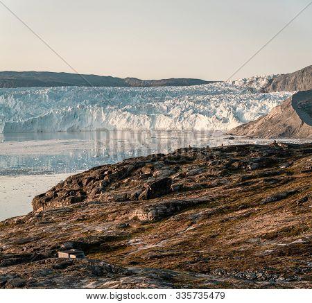 People Sitting Standing In Front Of Huge Glacier Wall Of Ice. Eqip Sermia Glacier Eqi Glacier In Gre