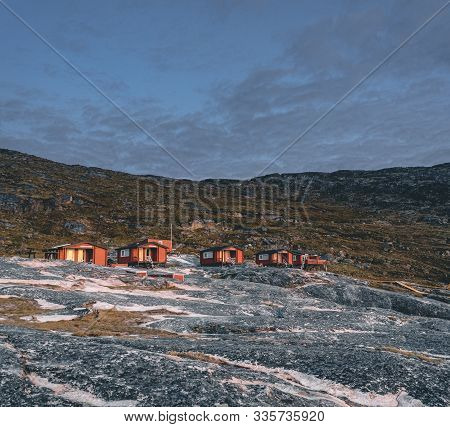Panoramic Image Of Camp Eqi At Eqip Sermia Glacier In Greenland. Nature Landscape With Lodge Cabins.