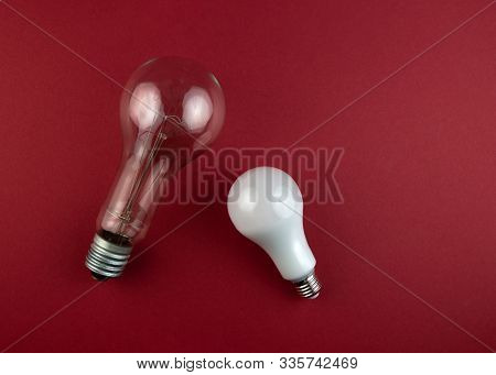 Old Incandescent Lamp And New Led Lamp On A Brawn Background. Energy Or Idea Concept.
