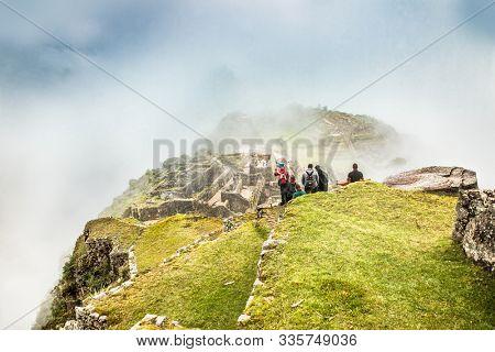 Machu Picchu, Peru-Jan 16, 2019: Tourists on site of Machu Picchu on cloudy day, Peru.