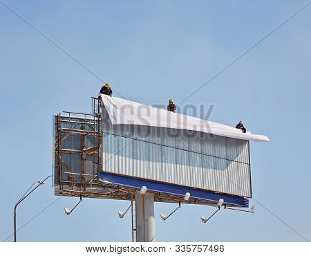 Worker Prepares Billboard To Installing New Advertisement. Industrial Climber Working On A Ladder -