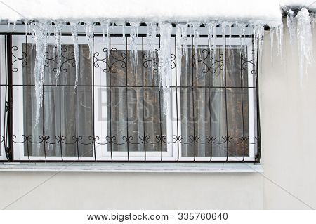 Frozen Ice Hanging Over The Window Of A Residential Building With Windows On The Balcony Is Dangerou