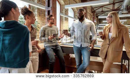 Portrait Of Mixed Race Business Team Having Coffeebreak In Office. Five Colleagues In Casual Wear Ar