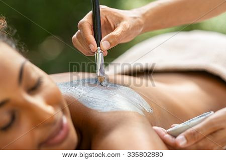 Hands of masseuse applying mud mask on african woman back. Young african american girl relaxing while beautician applying exfoliation clay on shoulder. Woman at resort doing clay mask exfoliation.