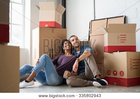 Young couple resting after moving into a new home and daydreaming. Multiethnic contemplative couple sitting on floor and thinking  while looking up. Happy couple buy new apartment and plan a family.
