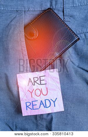 Text sign showing Are You Ready. Conceptual photo Alertness Preparedness Urgency Game Start Hurry Wide awake Small little wallet inside man trousers front pocket near notation paper. poster