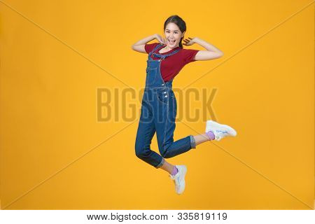 Studio Shot Of Young And Beautiful  Cute Asian Girl Wear Lovely Jeans Clothes Jumping  High With Fee