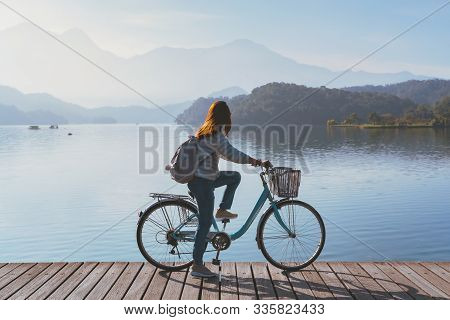 Young Woman Riding Bicycle On Sun Moon Lake Bike Trail, Travel Lifestyle Concept