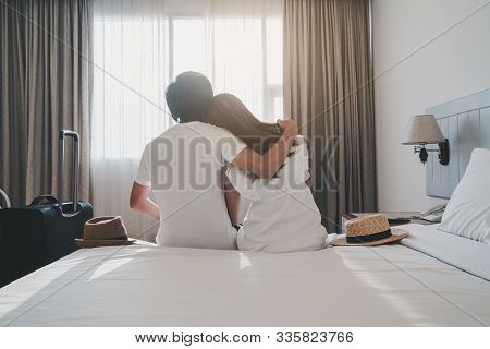 Young Couple Traveler With Luggage Sitting On Bed In Hotel Room On Summer Vacation