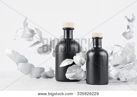 Elegant Blank Black Bottles For Cosmetic Or Home Decor On Soft Light White Wood Table With Silver Le