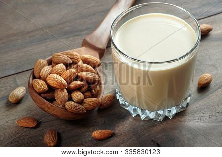 Almond Milk In A Glass On A Wooden Table. Almonds In A Wooden Spoon And A Glass Of Almond Milk