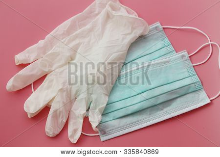 Two Disposable Medical Masks And A Pair Of Latex Gloves.