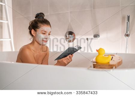 Bath at home woman relaxing taking a warm bath reading book cozy enjoying free time putting facial clay mask pampering weekend. Bubble bath spa time.