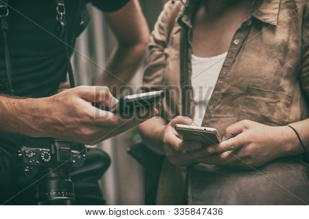 People using mobile phones holding smartphones travel lifestyle. Closeup of hands texting on smart cellphone tech devices tourists woman and man lost searching for directions.
