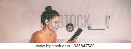 Woman putting face mask clay product reading a book relaxing in hot bath on unwind spa pampering weekend in luxury resort banner panorama. Asian girl taking a bath in bathtub.
