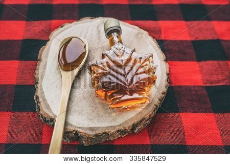Maple syrup bottle Quebec cultural food traditional harvest top view on buffalo dining tablecloth background. Canada grade A amber sweet liquid in wooden spoon from sugar shack cabane a sucre farm.