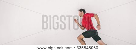 Running man runner training doing city run sprinting along wall outdoor white background. Male athlete profile doing sprint hiit high intensity interval training triathlon. Banner panorama.