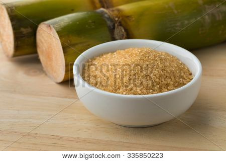 Bowl with cane sugar and fresh sugar cane in the background