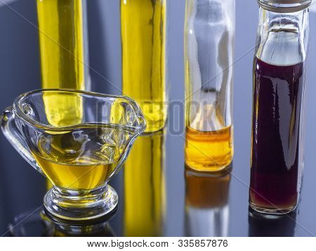 Vegetable Oil Is Poured Into Glass Bottles And Sauceboat. Bottles Of Vegetable Oil Reflected On The