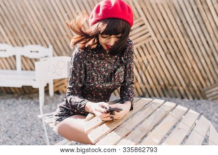 Gorgeous Girl With Short Hairstyle In Vintage Overall Sitting At Outdoor Cafe With Iphone, Checking