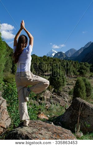 Young woman is practicing yoga in Tree Pose (Vrikshasana) pose at mountain
