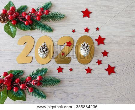 New Year's composition. Christmas tree branches with berries on a wooden background.  New 2020 year concept. Flat lay. Top view