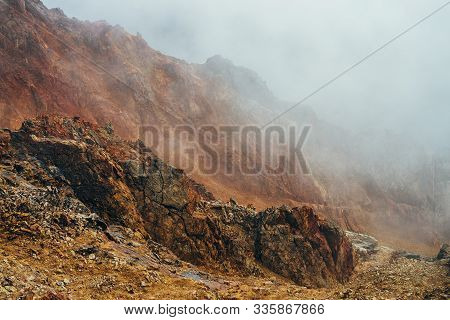 Atmospheric Alpine Landscape With Craggy Mountains Inside Clouds. Wonderful Highland Scenery With Ro