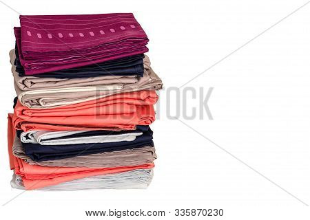A Stack Of Folded Clean Sheets And Duvet Covers On A White Background. Bedding After Washing. Closeu