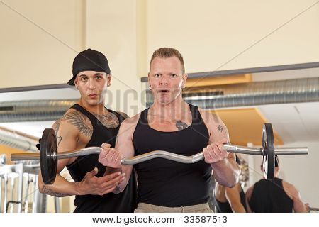 man in his forties exercising in gym with trainer