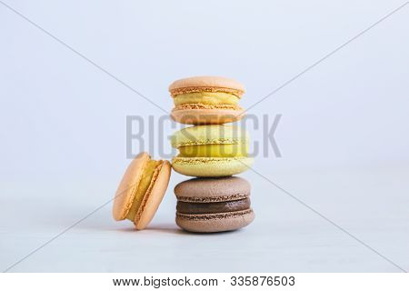 Tasty French Macarons On A White Wooden Table. Multicolored Macarons. White Background. Minimal Conc