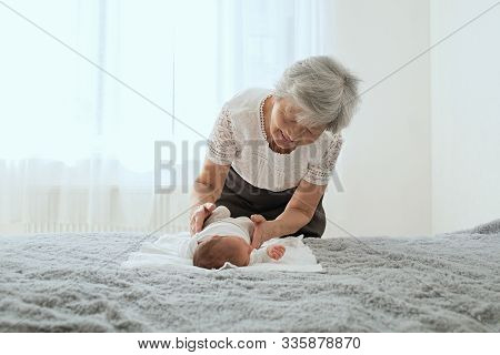 Great-grandmother Plays With A Newborn Great-granddaughter. The Baby Lies In The Arms Of The Grandmo