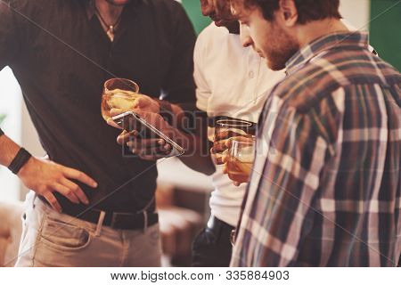 Group Of Multietnic Friends Guys With Glasses Of Whiskey. Concept Party, Bachelor Party Barbershop.