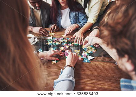 Group Of Creative Multietnic Friends Sitting At Wooden Table. People Having Fun While Playing Board