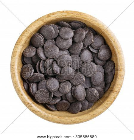 Dark Unsweetened Chocolate Chips In Wooden Bowl Isolated On White. Top View.