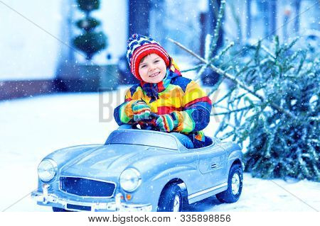 Beautiful Little Smiling Kid Boy Driving Toy Car With Christmas Tree. Happy Child In Winter Fashion