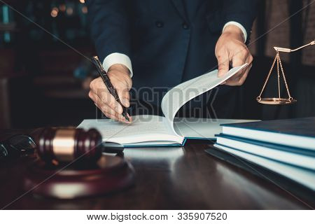 Justice And Law Concept. Gavel On Sounding Block In Hand's Male Judge At A Courtroom, Working With D