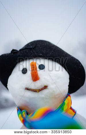 Funny Snowman In Stylish Hat And Scarf On Snowy Field. Snowman Gentleman In Winter Hat. Cute Little