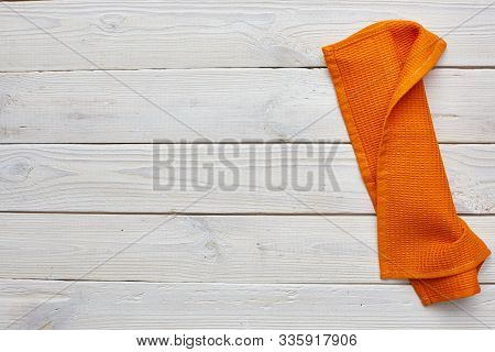 Orange Dishcloth On White Wooden Boards. Copyspace. Top View.