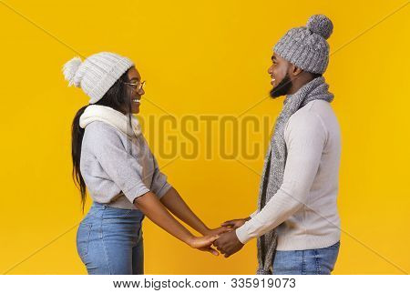 Side view of affectionate african couple standing together, holding hands and looking at each others eyes against yellow studio background, winter set poster