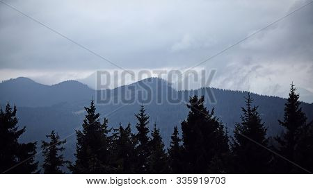 Mountains And Forrest Landscape With Cloudy Sky And Foggy Sky. Fir Trees With Misty Weather Hiking H