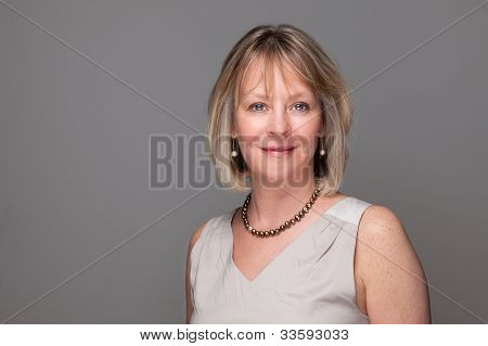 Head Shot of Attractive Smiling Elegant Woman on Grey Background
