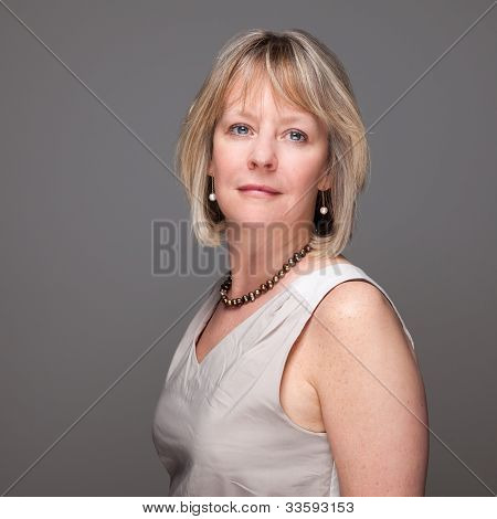 Attractive Middle Age Woman with Enigmatic Look on Grey Background