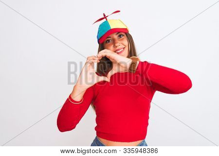 Young beautiful girl wearing fanny cap with propeller standing over isolated white background smiling in love showing heart symbol and shape with hands. Romantic concept.