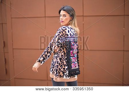 Young beautiful wearing animal print cardigan standing on backview at the town