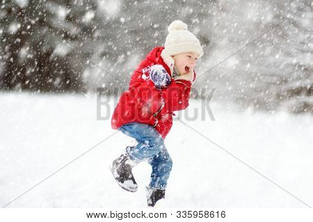 Adorable Young Girl Having Fun In Beautiful Winter Park During Snowfall. Cute Child Playing In A Sno